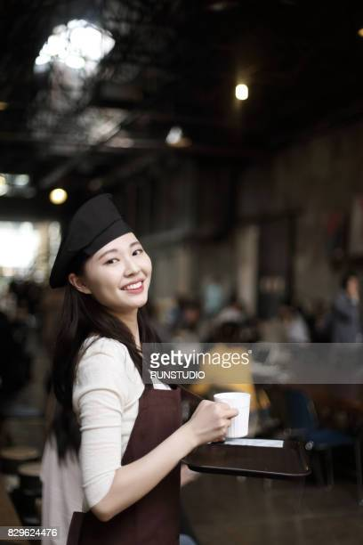 Portrait smiling waitress carrying tray with a cup of coffee