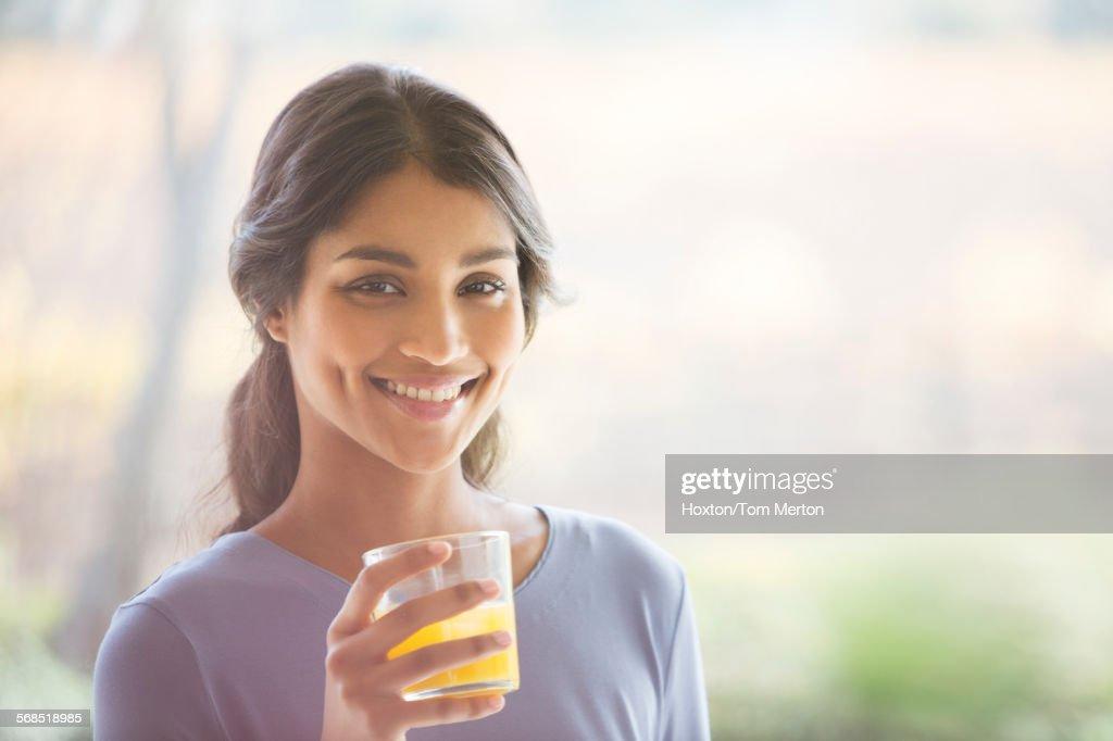 Portrait smiling woman drinking orange juice