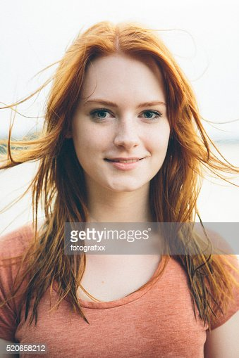 portrait smiling young redhead woman on nature background