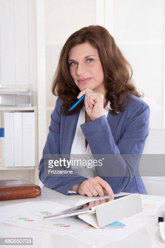 Retrato: Más exitosa empresaria sentado en su oficina. : Foto de stock