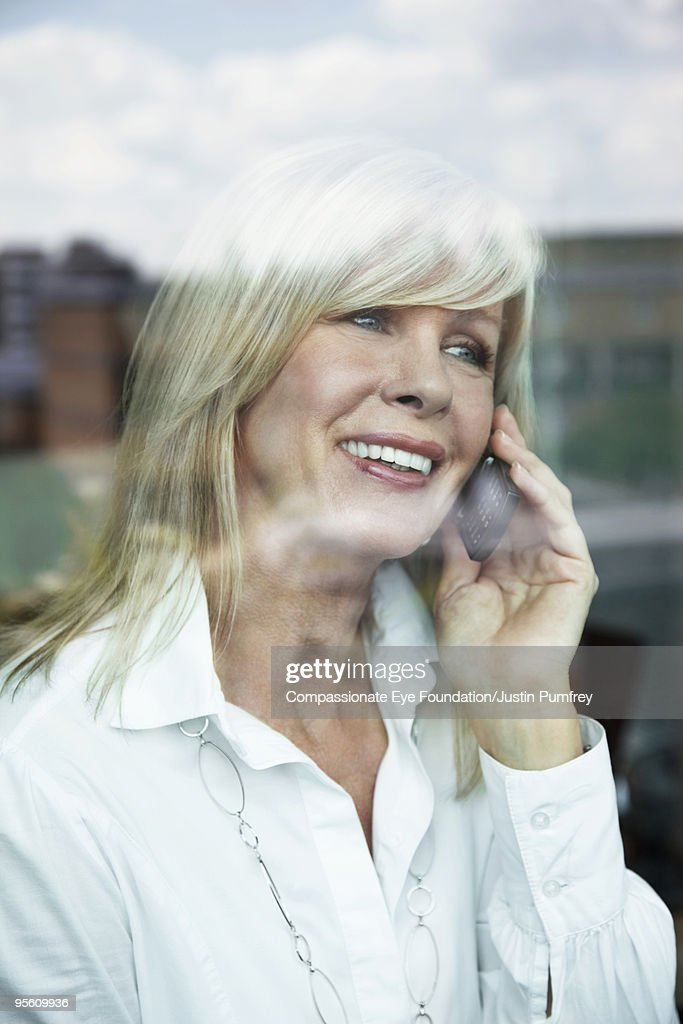 Portrait through a window of a woman on a cell  : Stock Photo