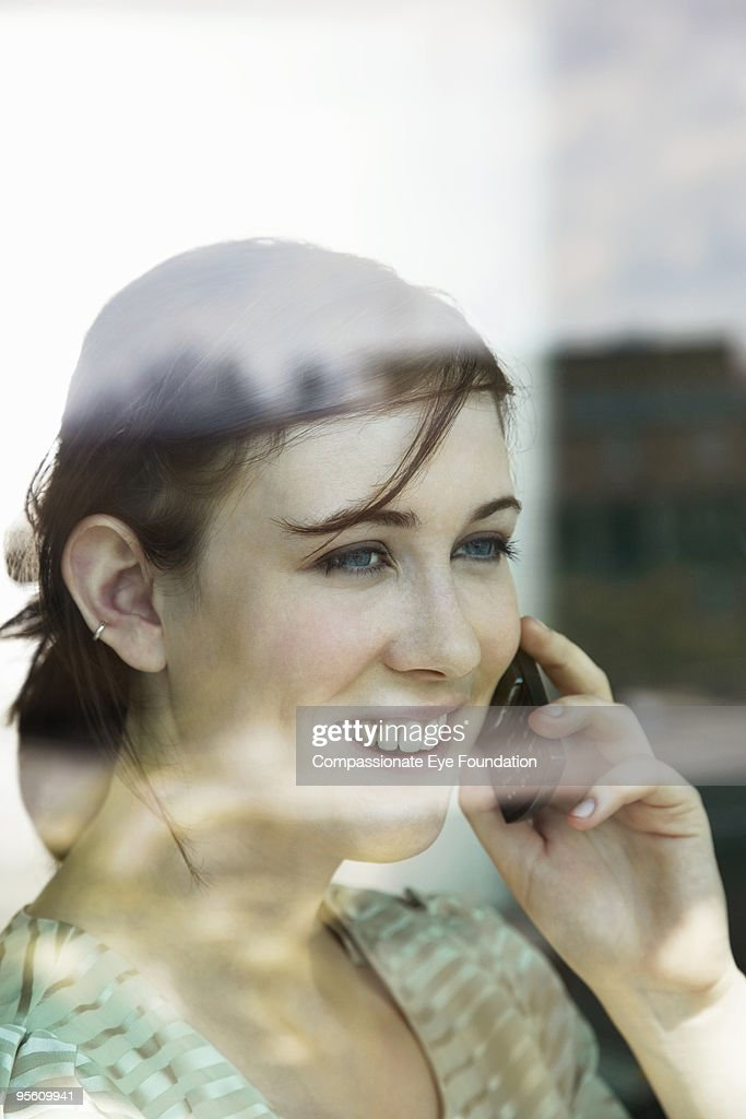 Portrait through a window of a woman on a phone