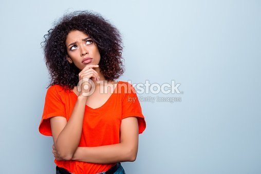 Portrait with copy space empty place of thoughtful minded woman with modern hairdo holding hand on chin looking up trying to find solution isolated on grey background : Stock Photo