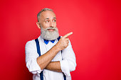Portrait with copy space of minded, ponder, professional, retro stylist, barber with blue bowtie and suspenders pointing on empty place, product with forefinger, isolated on red background