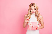Portrait with copyspace, empty place of pretty charming elegant girlfriend celebrating 8-march, valentine day, opening packed gift box isolated on pink background