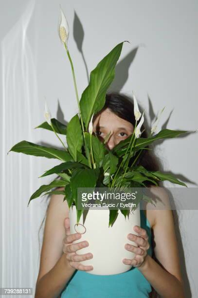 Portrait Woman Hiding Behind Potted Plant Against Wall
