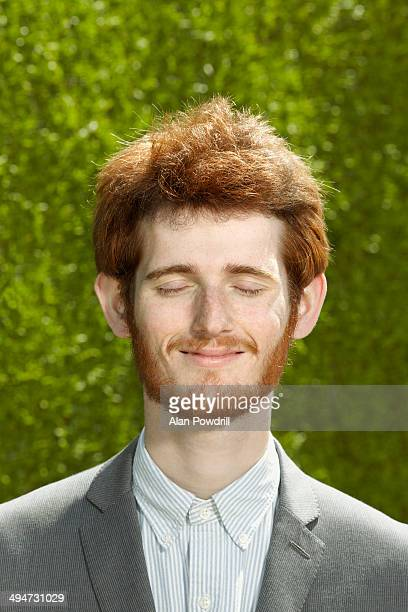 Portrait young red haired man with eyes closed
