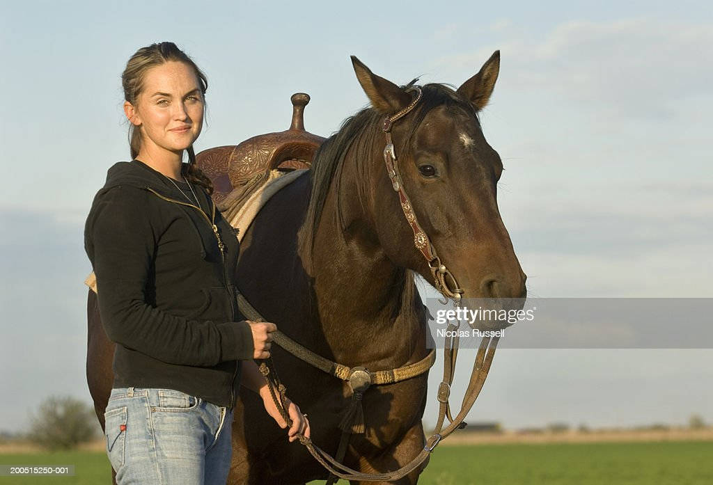 Portrait, young woman holding horse. : Stock Photo