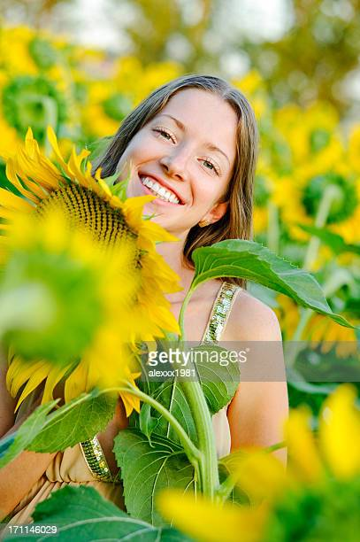 Portrait young woman in sunflower field on sunset