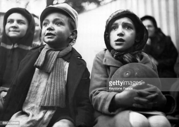 Portraits d'enfants regardant avec intérêt un spectacle du Guignol des Buttes Chaumont à Paris France le 28 février 1940