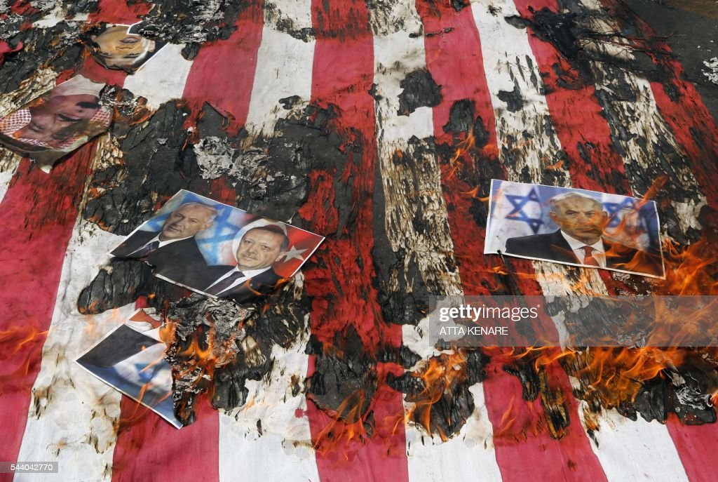 Portraits of Bahraini King Hamad (top L), Israeli Prime Minister Benjamin Netanyahu and Turkish President Recep Tayyip Erdogan lie on a US flag in flames during a parade marking al-Quds (Jerusalem) Day in Tehran on July 01, 2016. Tens of thousands joined pro-Palestinian rallies in Tehran, as the annual Quds Day protests take on broader meaning for a region mired in bitter disputes and war. KENARE