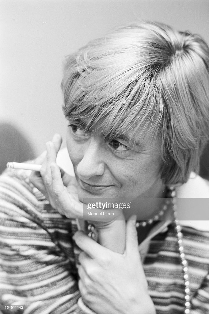 Portraits of Francoise Sagan in 1974 wearing a striped sweater and a polostyle pearl necklace smoking a cigarette one hand under the chin