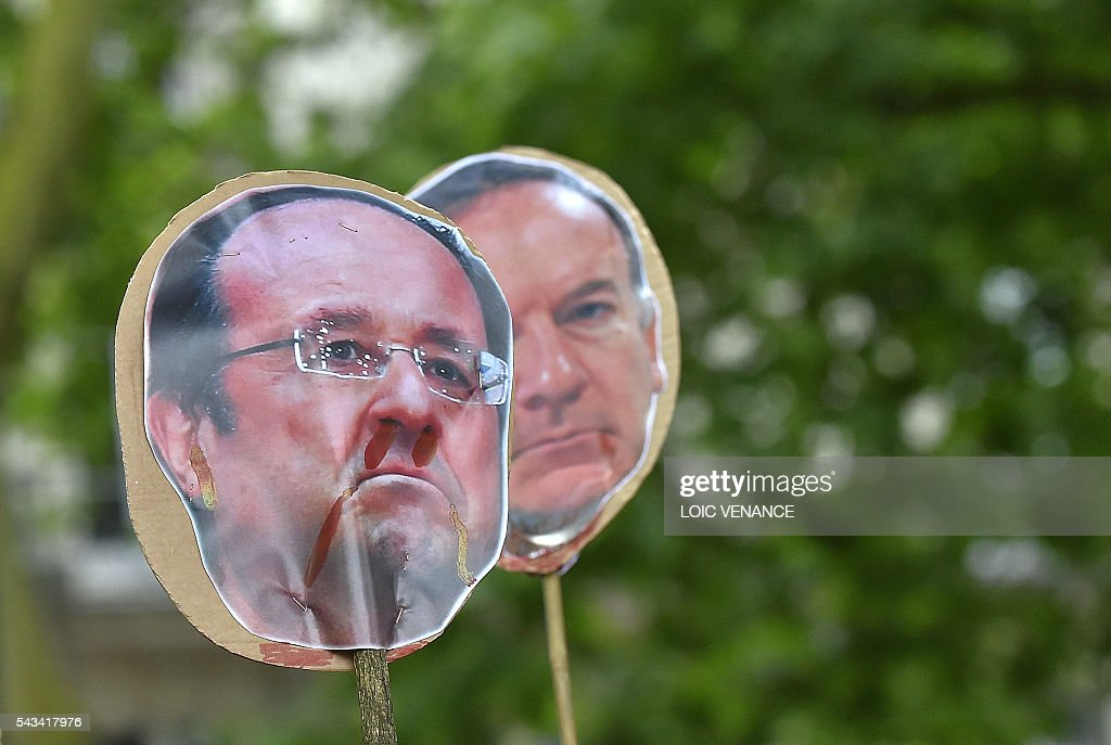 Portraits of French President Francois Hollande (L) and French employers' association Medef president Pierre Gattaz (R) are pictured during a protest against controversial labour reforms, on June 28, 2016 in Nantes, western France. People took to the streets in France on June 28 in the latest protest march in a marathon campaign against the French Socialist government's job market reforms. Last month the government used a constitutional manoeuvre to push the bill through the lower house without a vote in the face of opposition from Socialist backbenchers. / AFP / LOIC