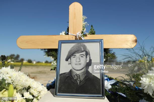 A portraits of Georgiou Theodoulos Theodoulou stands at his grave following his funeral on March 5 2017 in Pera Chorio Nisou Cyprus Theodoulou was an...