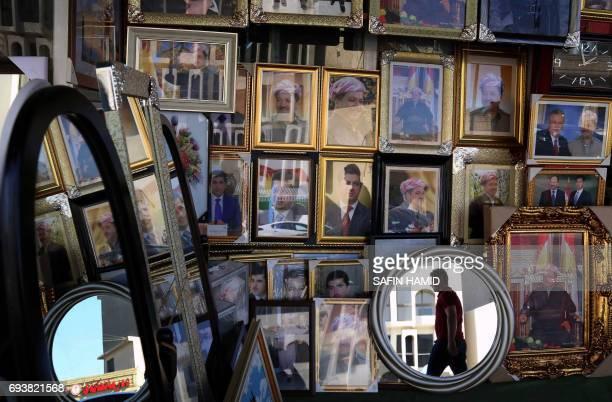 TOPSHOT Portraits of Iraqi Kurdish leader Massud Barzani are seen hanging in a store in Arbil the capital of the autonomous Kurdish region of...