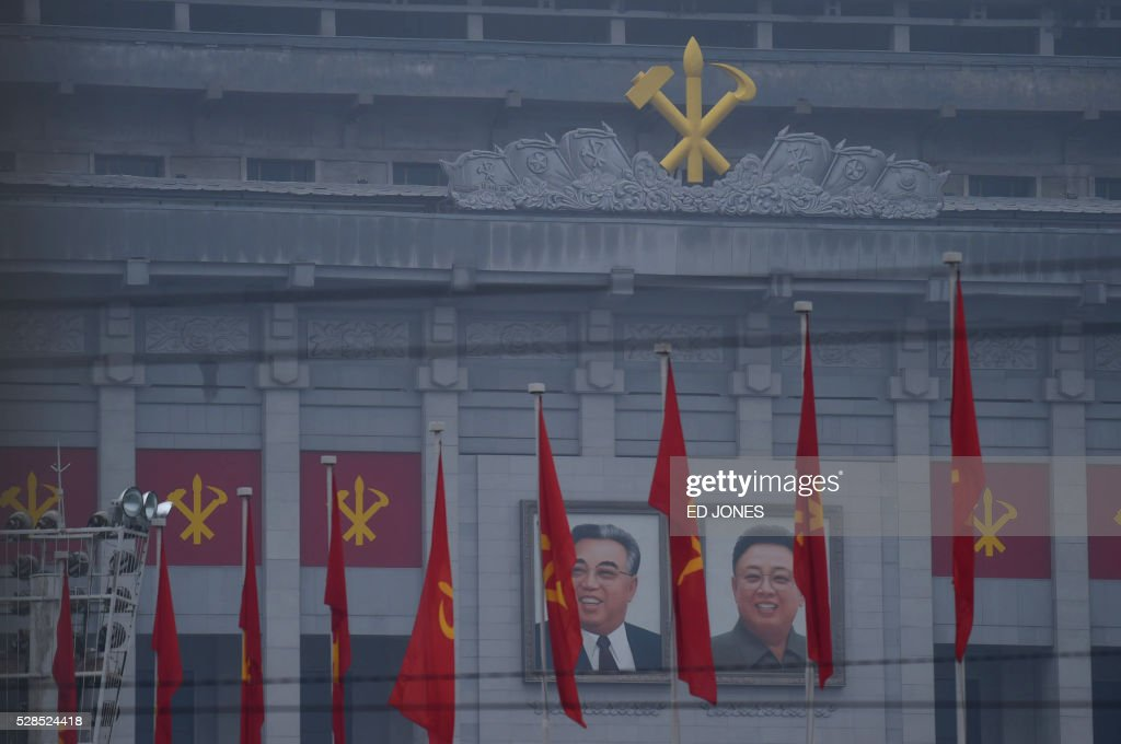 Portraits of late North Korean leaders Kim Il-Sung (L) and Kim Jong-Il (R) are displayed past flags on The April 25 Palace, venue of the Workers' Party Congress, ahead of the event in Pyongyang on May 6, 2016. North Korea will on May 6 launch its highest-level ruling party meeting in almost 40 years, with delegates set to heap praise on its nuclear arsenal as a 'precious sword' amid fears of a fresh atomic test. / AFP / Ed Jones