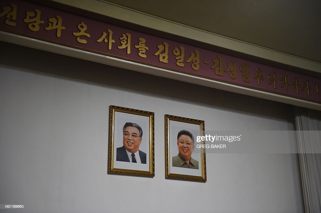 Portraits of late North Korean leaders Kim Il-Sung (L) and Kim Jong-Il hang on a wall at the North Korean embassy in Beijing on July 28, 2015. North Korea's nuclear weapons are 'not a plaything' and their future is not up for negotiation, Pyongyang's ambassador to China said on July 28, ahead of a visit by a US envoy. AFP PHOTO / GREG BAKER