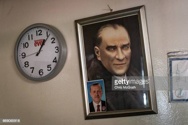 Portraits of Mustafa Kemal Ataturk and Turkish President Recep Tayyip Erdogan are seen next to an 'Evet' clock on a wall of a teahouse on April 16...