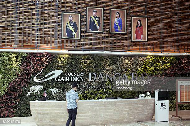 Portraits of the Royal family of Johor are displayed above signage for the Country Garden Holdings Co Danga Bay development in the reception of the...