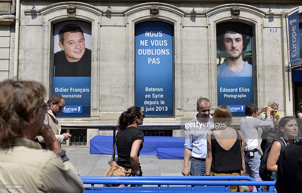 Portraits of the two French radio journalists Didier Francois (L) and Edouard Elias kidnapped in Syria on June 6, 2013 are hung on the windows of Europe 1 radio station studio in Paris on July 9, 2013 as people take part in a rally in their support. AFP PHOTO / ERIC FEFERBERG