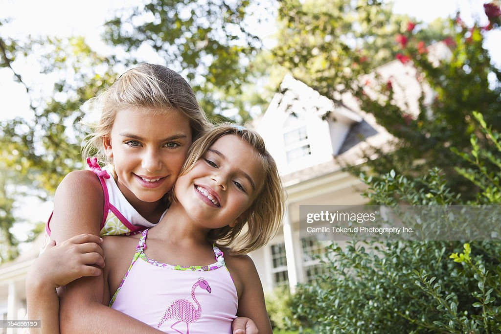 Portraits of two sisters hugging : Stock Photo
