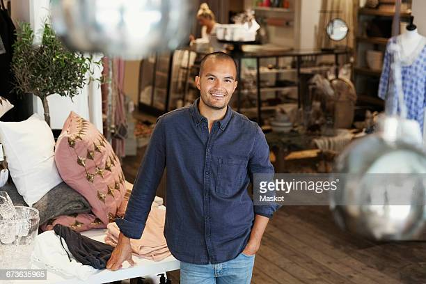 Portriat of smiling male owner standing by clothes on table at store