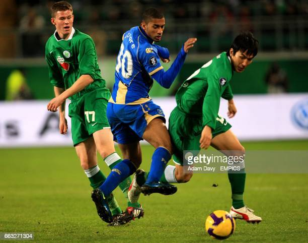 Portsmouth's Armand Traore is challenged by Wolfsburg's Makoto Hasebe and Alexander Madlung