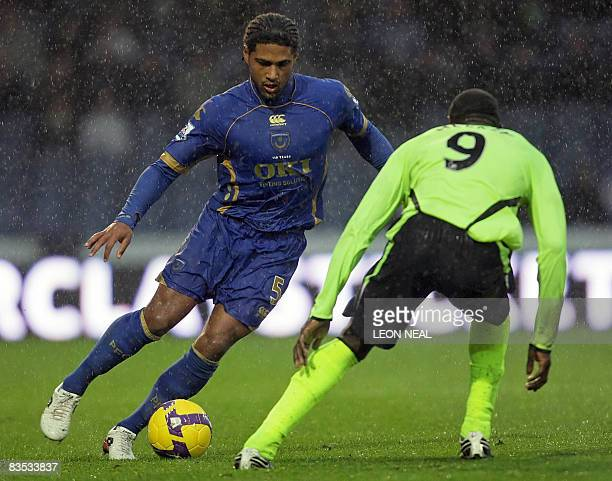 Portsmouth's Glen Johnson evades a tackle by Wigan's Emile Heskey during a Premiership match at Fratton Park in Portsmouth on November 1 2008 Wigan...