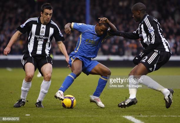 Portsmouth's Jermain Defoe battles for the ball with Newcastle United's Sanchez Jose Enrique and Sebastien Bassong