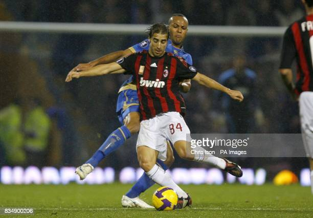 Portsmouth's Mathieu Flamini is challenged by Portsmouth's Younes Kaboul as they battle for the ball
