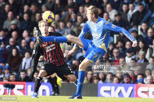 Portsmouth's Peter Crouch controls the ball under pressure from Manchester City's Pablo Zabaleta