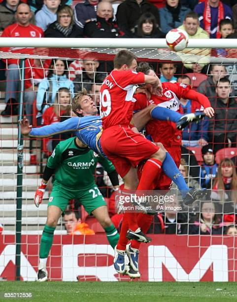 Portsmouth's Peter Crouch has a shot on goal as Middlesbrough's Tony McMahon and Robert Huth challenge him for the ball