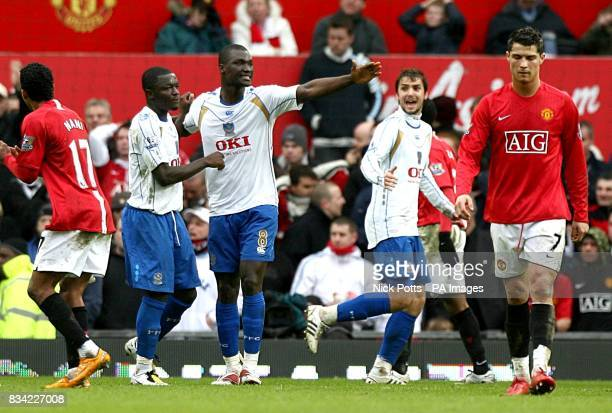 Portsmouth's Sulley Muntari celebrates scoring the opening goal of the match from the penalty spot as Manchester United's Cristiano Ronaldo stands...