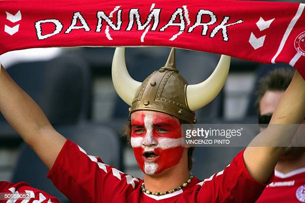 A Danish supporter with the colours of his country painted on his face holds his team's banner 14 June 2004 at Henriques stadium in Guimaraes as he...