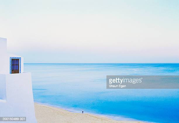 Portugal, Algarve, Albufeira, man on beach looking out to sea