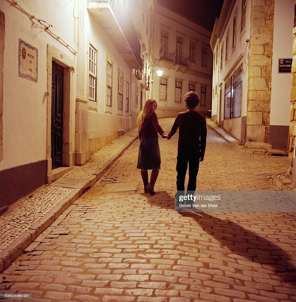 Portugal, Algarve, Lagos, couple walking on street at night, rear view : Stock Photo