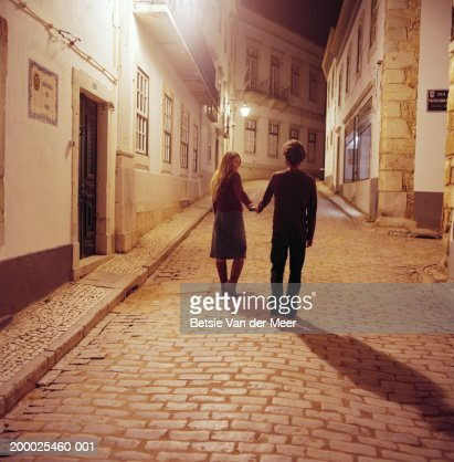Portugal, Algarve, Lagos, couple walking on street at night, rear view : Stock Photo