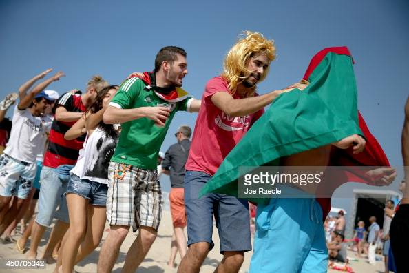 Portugal and German soccer fans create a conga line as they wait for their teams to take to the field as they watch on a giant screen at the FIFA...