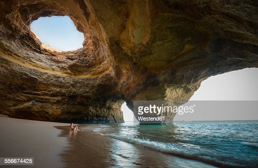 Portugal, beach of Benagil, cave, woman sitting at seafront