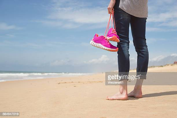 Portugal, Faro, barefoot woman on the beach carrying her pink sneakers