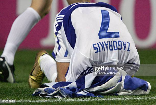 Greece's captain Theodoros Zagorakis buries his head in a Greek flag 04 july 2004 at the Stadio Da Luz in Lisbon after winning the Euro 2004 final...