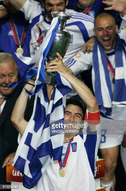 Greece's captain Theodoros Zagorakis surrounded by team members holds up the trophy 04 July 2004 at Stadio da Luz in Lisbon after the Euro 2004 final...