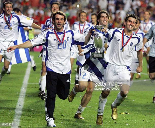Greece's midfielder Georgios Karagounis and captain Theodoros Zagorakis hold the trophy 04 july 2004 at the Stadio Da Luz in Lisbon after the Euro...