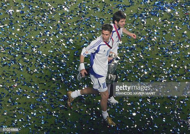 Greece's midfielder Vasileios Tsiartas and Georgios Karagounis run with the cup 04 July 2004 at Stadio da Luz in Lisbon after the Euro 2004 final...