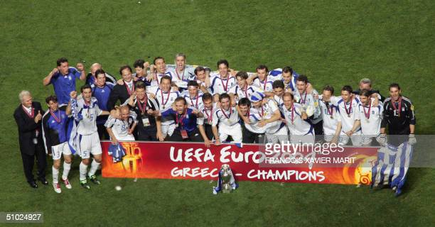 Greek players and staff members pose for photographers04 July 2004 at Stadio da Luz in Lisbon after the Euro 2004 final football match between...