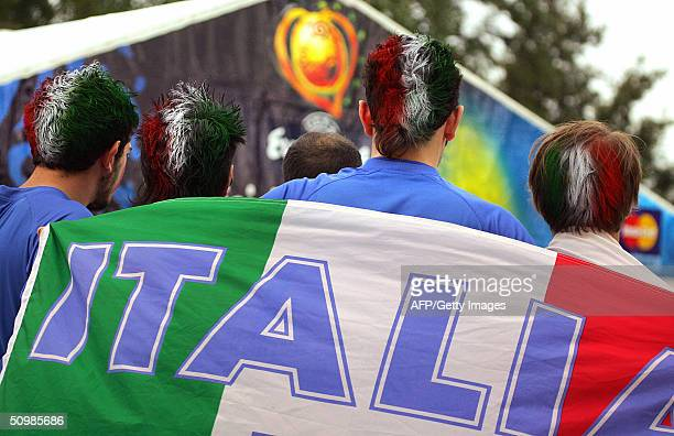 Italian supporters hold their national flag 22 June 2004 near Henriques stadium in Guimaraes before the beginning of the Euro 2004 group C football...