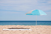Portugal, Lagos, Beach towel and sunshade on beach
