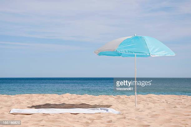 Portugal, Lagos, Beach towel and sunshade on beach