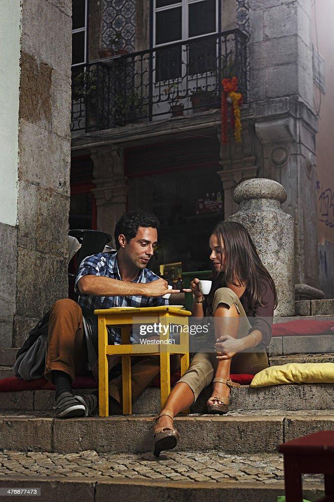 Portugal, Lisboa, Bairro Alto, young couple sitting at street cafe at dusk