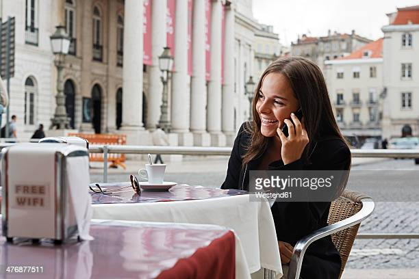 Portugal, Lisboa, Baixa, Rossio, Praca Dom Pedro IV, Teatro Nacional, young woman telephoning at street cafe